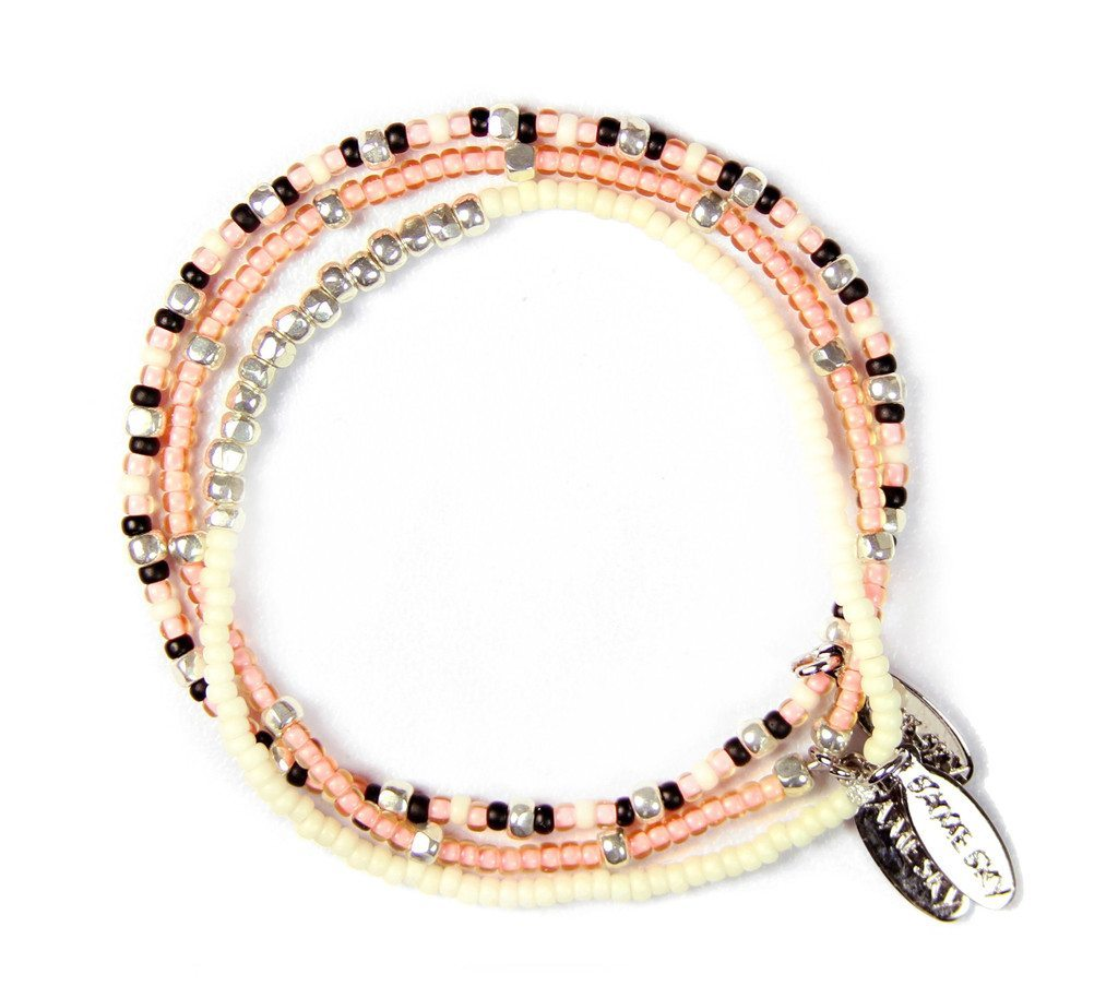 photo of a pink, black and white triple strand bracelet with silver charms