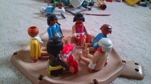 Playmobil figures grouped around a campfire