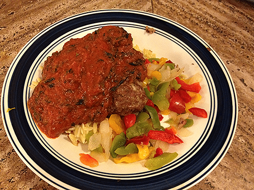 An image of meatballs with pasta sauce and vegetables on a dinner plate.