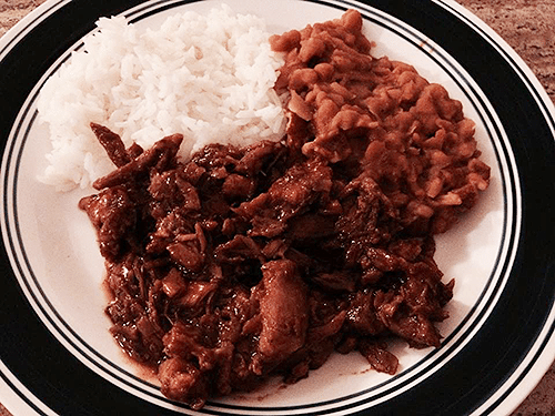 Image of shredded pork, baked beans, and white rice on a dinner plate.