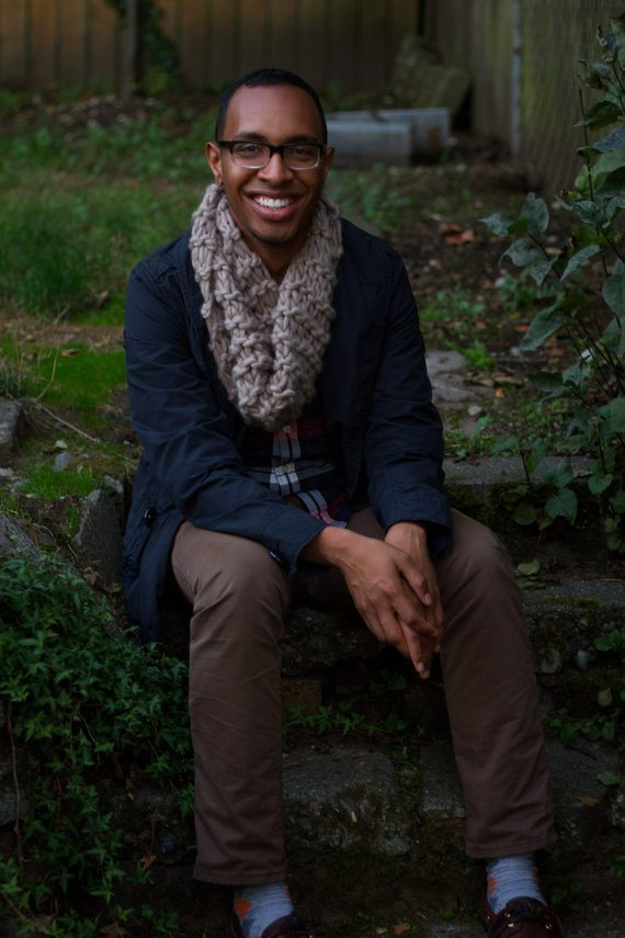 Photo of super hot young black man sitting in a garden wearing a chunky brown knitted scarf, a navy sweater and brown pants