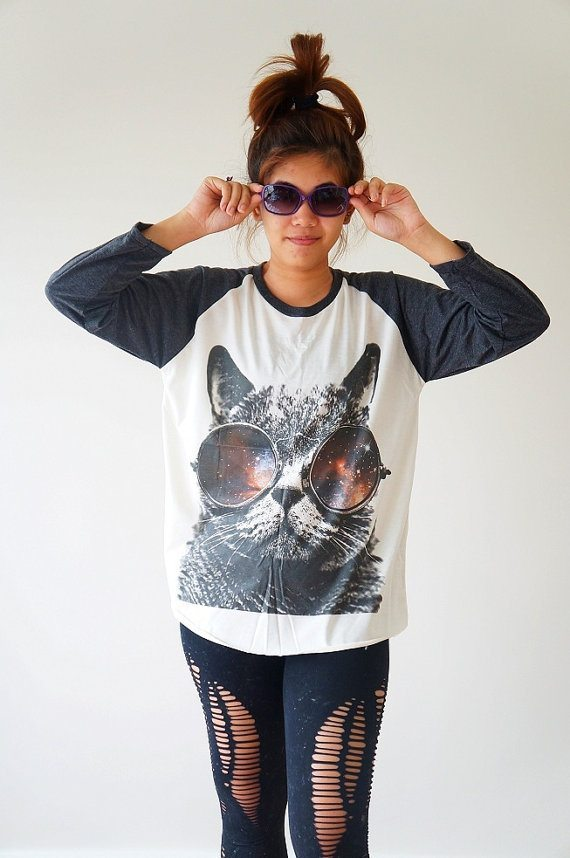 photo of a young woman wearing a black and white baseball tee with a huge screened picture of a cat wearing sunglasses