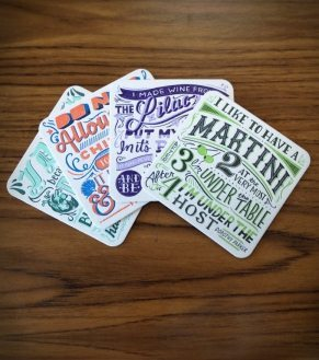 photo of four drink coasters with various quotes on them in a fancy font on a wood table