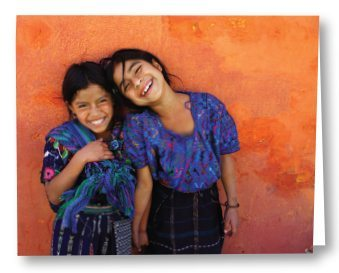 photo of two young girld in blue laughing and leaning against an orange wall