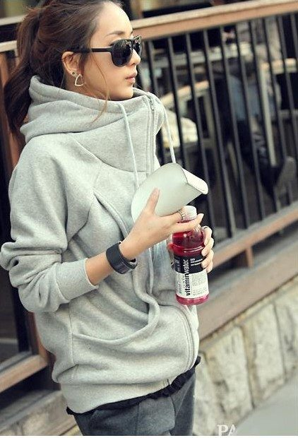 photo of a brown haired young woman leaning against a fence holding a vitamin water wearing a cute grey hoodie