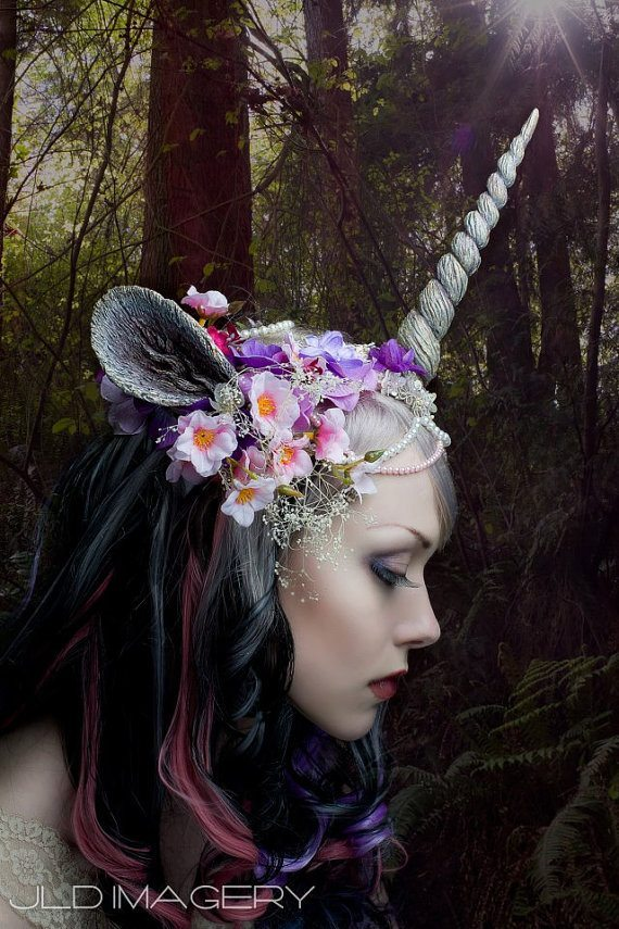 profile photo of a woman with black hair wearing a unicorn horn with flowers and other decorative elements