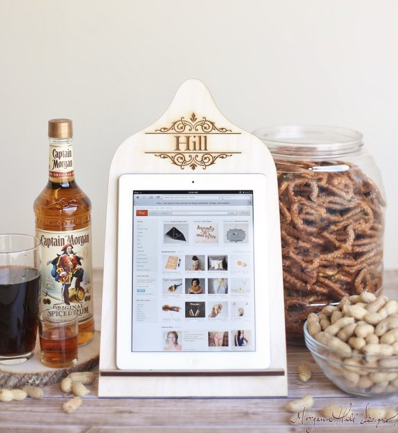 photo of a light wood iPad stand with the word Hill laser cut into it. A bottle of booze and bowls of snacks in the background