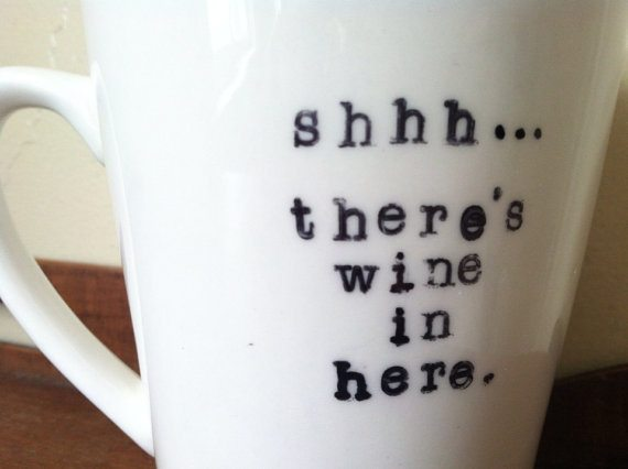 "photo of a white mug that says ""Shhh... there's wine in here"" in black"