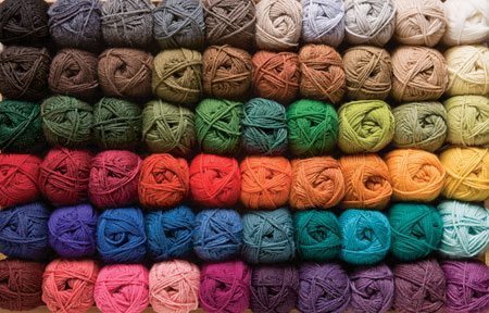 A picture of many balls of yarn stacked and organized by color.