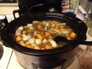 A crock pot full of Ginger and Root Veggie Soup, with a ladle in it.