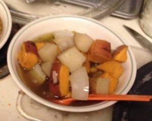 A Bowl of Ginger and Root Veggie Soup, with a table spoon being used as a spoon.
