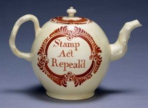 "A picture of a teapot from 1766 printed with te words ""Stamp act repeal'd."""