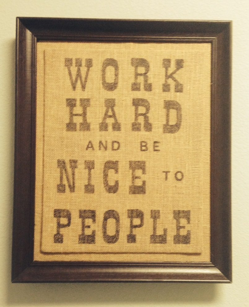 "a brown frame around a burlap wrapped canvas that says ""Work Hard and be Nice to People"""