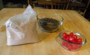 Picture of a bag of cake mix, a bowl of cherries, and a bowl of chocolate chips