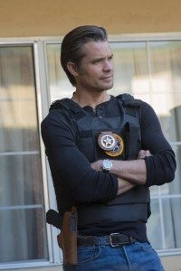 Raylan, arms crossed, in his U.S. Marshal gear
