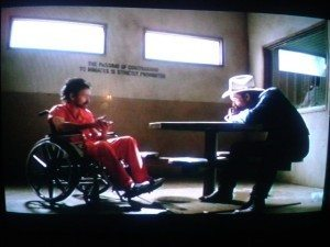 Raylan sitting at a table with his head on his hands, listening to Dickie Bennett