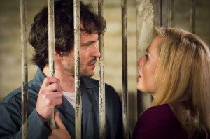 Bedelia is grabbing the cage bars while talking to Will.