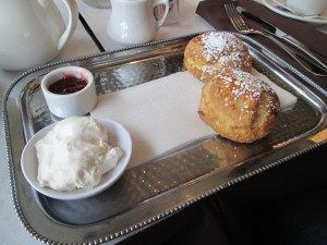 A plate of scones, jam, and clotted cream