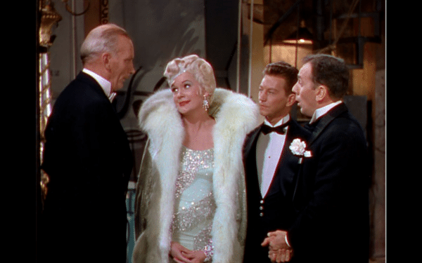 A picture of Lina Lamont with three men in tuxedos.
