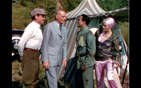 A picture of four people dressed in movie costumes talking in front of a striped tent.