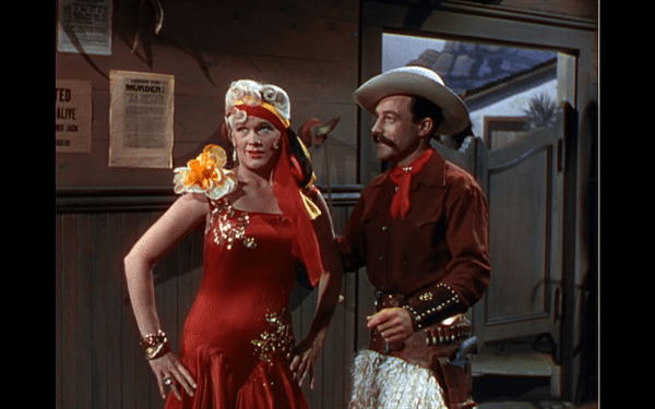 Lina Lamont in a red dress next to a man in a cowboy costume.