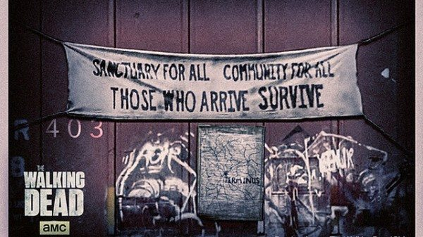 "A banner reads ""Sanctuary for all, Community for all, Those who arrive survive"""