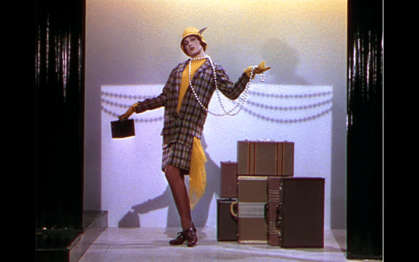 Model posing in a tweed and yellow dress with a long string of pearls