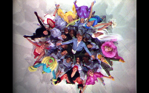 Aerial shot of Don in the center of a circle of glamorous models