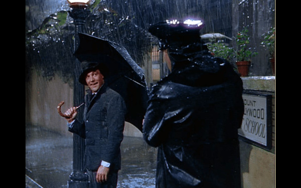 Don, soaking wet and holding an umbrella while talking to the police officer