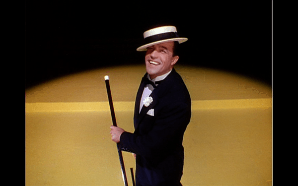 Don in a spotlight, with a hat and cane