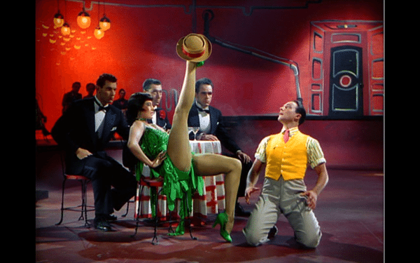 Cyd Charisse doing a seated high kick, with Don's hat on her foot, while he kneels in front of her, dazed