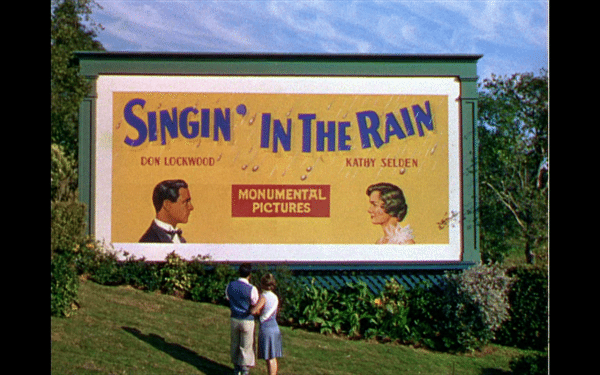 Don and Kathy embrace in front of a billboard for Singin' in the Rain with their pictures on it