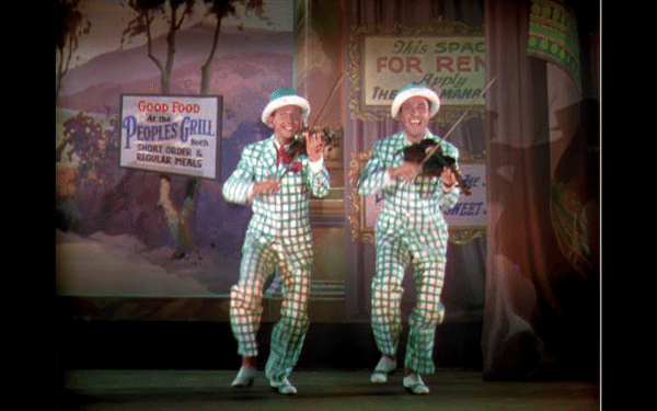 Don and Cosmo in green plaid suits, playing fiddles while singing and dancing