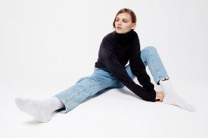 Thin white person in a long sleeved turtleneck, pale jeans, and white socks stretches out.