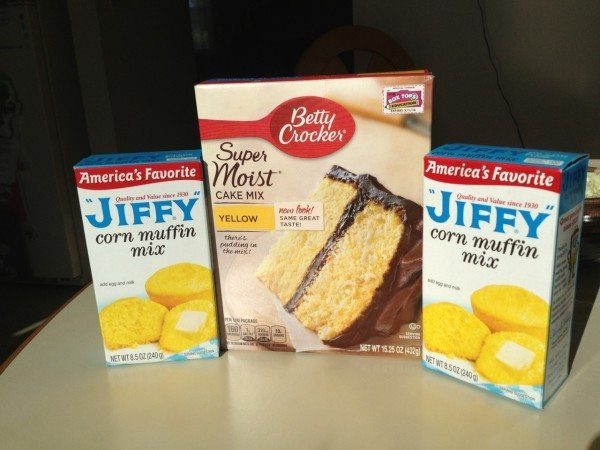 A box of Betty Crocker yellow cake mix and two boxes of Jiffy corn muffin mix
