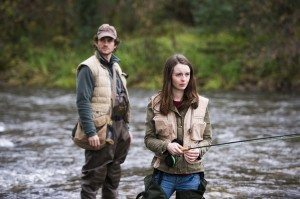 Will and Abigail Hobbs stand in a river while fly fishing.