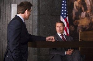 Hannibal sits at the witness stand while taking questions from Will Graham's lawyer