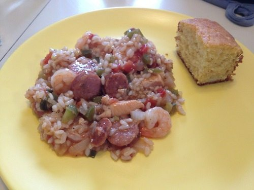A yellow plate with a serving of jambalaya and a thick slice of cornbread.