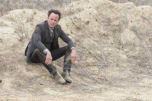 Boyd sitting on a desert hillside alone