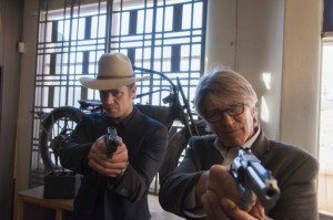 Timothy Olyphant and Eric Roberts as Raylan and Miller, holding guns on Jay and Roscoe (unseen)