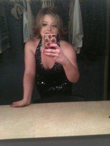 Emma selfie in a low-cut sparkly black dress