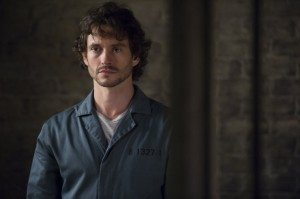 Will Graham stands up and can be seen through his cell