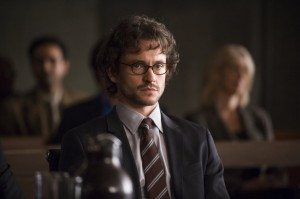 Will Graham is seated at a table in court in a nice suit.