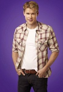Cast photo from Glee of Chord Overstreet as Sam. He's standing in front of a purple backdrop with his hands in the pockets of his jeans and is wearing a plaid button-down over a white tee.