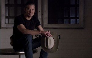 Raylan sitting on a table talking to Ava.