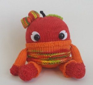 a red knitted monster with a bow on her head