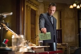 Holmes holding up a sign for a robotic mosquito in a jar.