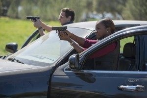 Tim and Rachel with guns drawn at their car
