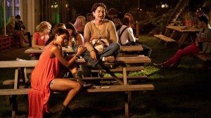 Two Indian women sit on a picnic table. One is crying.