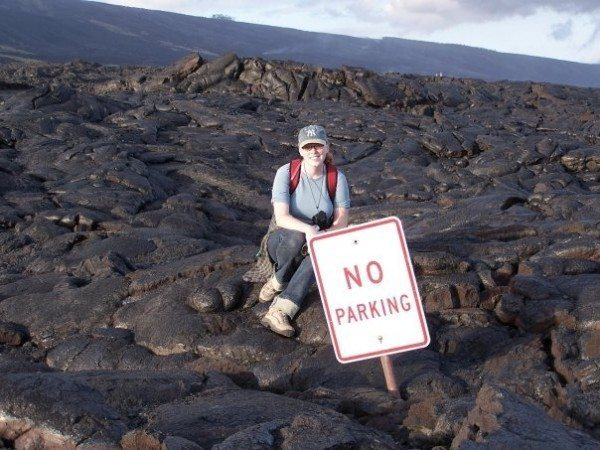 Author sits on lava next to a No Parking sign that's been almost fully buried.